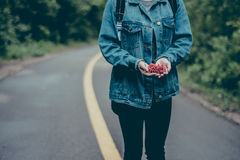 Woman in Blue Denim Jacket Holding Fruits Standing on Black Asphalt Road Stock Images