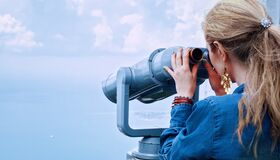 Woman in Blue Denim Jacket Holding a Gray Steel Tower Viewer Stock Images
