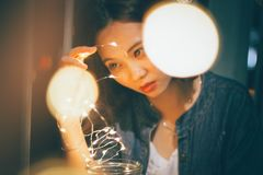 Woman In Blue Denim Jacket Holding String Lights stock photo