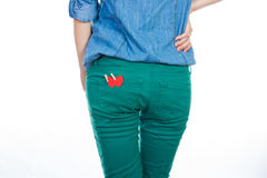 A woman in a blue denim shirt and green jeans standing isolated on white background with a red paper heart in your back pocket. Figure of a girl. A woman in a Royalty Free Stock Image