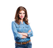 Woman in blue denim shirt and jeans, studio shot. Young beautiful woman in blue denim shirt and jeans, arms crossed, studio shot on white background, isolated Royalty Free Stock Image