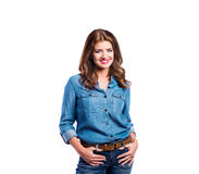Woman in blue denim shirt and jeans, studio shot. Young beautiful woman in blue denim shirt and jeans, hands in pockets. Studio shot on white background Stock Image