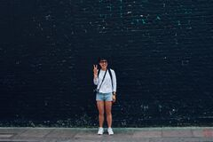 Woman in Blue Denim Shorts Standing in Front of Black Brick Wall Royalty Free Stock Photo
