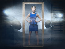 A woman in a blue dress on a glamor studio background Royalty Free Stock Images