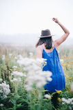 Woman in Blue Dress and Gray Fedora Hat on Flower Field Royalty Free Stock Photos