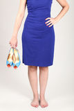 A woman with a blue dress holding high heels Stock Photos