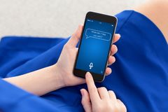 Woman in blue dress holding phone with app personal assistant Stock Images