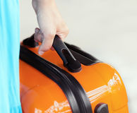 Woman in blue dress holds orange suitcase in hand Stock Photography