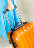 Woman in blue dress holds orange suitcase in hand Stock Photos