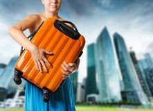 Woman in blue dress holds orange suitcase in hands Royalty Free Stock Image