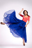 Woman in blue dress kicking Stock Photography