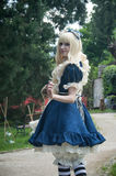 Woman with blue dress like Alice in wonderland by Sakizou japanese artist in park way at cosplay exhibition event. WESSERLING - France - 21 May 2017 - woman with Royalty Free Stock Images