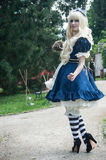 Woman with blue dress like Alice in wonderland by Sakizou japanese artist in park way at cosplay exhibition event Stock Photos