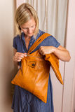 Woman In Blue Dress Looks Into a Light Brown Purse Royalty Free Stock Images