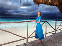 The woman in a blue dress looks at the sea Royalty Free Stock Photos