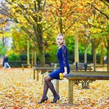 Woman in blue dress in the Luxembourg garden of Paris on a fall day. Beautiful young woman in blue dress in the Luxembourg garden of Paris on a fall day stock photos