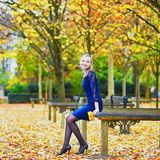 Woman in blue dress in the Luxembourg garden of Paris on a fall day. Beautiful young woman in blue dress in the Luxembourg garden of Paris on a fall day stock photography