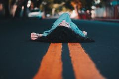 Woman in Blue Dress Lying Down on the Street Royalty Free Stock Image