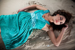 Woman in blue dress lying on sand dune Royalty Free Stock Image