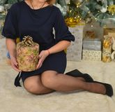 Woman in a blue dress sits under the tree and holds a gift box royalty free stock images