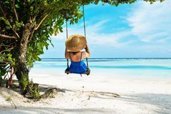 Woman in blue dress swinging at beach Royalty Free Stock Image