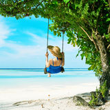 Woman in blue dress swinging at beach Stock Photos