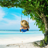 Woman in blue dress swinging at beach Stock Photo