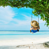 Woman in blue dress swinging at beach Royalty Free Stock Photography