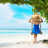 Woman in blue dress swinging at beach Stock Image