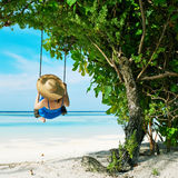 Woman in blue dress swinging at beach Stock Photography
