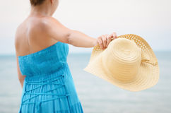 Woman in blue dress throws hat on the beach Royalty Free Stock Photography