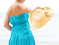 Woman in blue dress throws hat on the beach Stock Photography