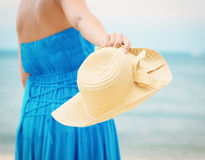 Woman in blue dress throws hat on the beach Royalty Free Stock Images