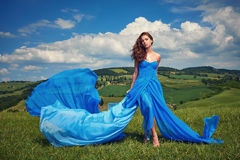 Woman in blue dress on Tuscany hills Royalty Free Stock Image