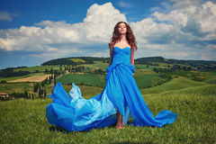 Woman in blue dress on Tuscany hills Stock Photos