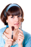 Woman in blue dress with two make-up brushes Stock Photography