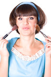 Woman in blue dress with two make-up brushes Royalty Free Stock Images