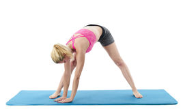 Woman on blue exercise mat doing yoga Royalty Free Stock Photo