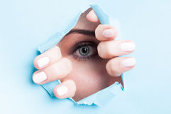 Woman blue eye with mascara looking thru ripped board Stock Photo