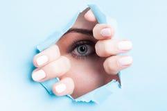 Woman blue eye with mascara looking thru ripped board Stock Photo