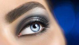 Woman blue eye with perfect makeup. Beautiful professional smokey eyes holiday make-up. Eyebrows shaping, eyes and eyelashes stock images
