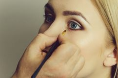 Woman with blue eyes getting makeup stock photos
