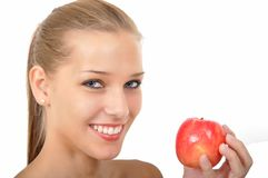 Woman with blue eyes holding an apple. Young woman with sparkling blue eyes holding an apple Royalty Free Stock Photo
