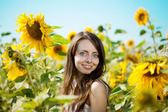 Woman with blue eyes with sunflowers Stock Photos
