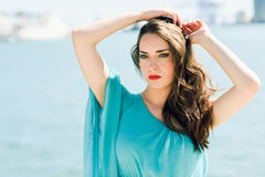 Woman with blue eyes wearing blue dress in the beach. Royalty Free Stock Images