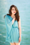 Woman with blue eyes wearing blue dress in the beach. Stock Image