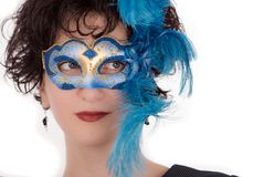 Woman with blue eyes wearing a feathered Venetian mask Stock Image