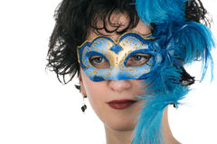 Woman with blue eyes wearing a feathered Venetian mask Royalty Free Stock Photos