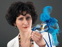 Woman with blue eyes wearing a feathered Venetian mask Royalty Free Stock Photo