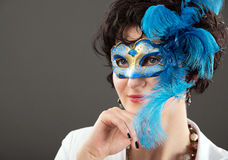 Woman with blue eyes wearing a feathered Venetian mask Stock Photos